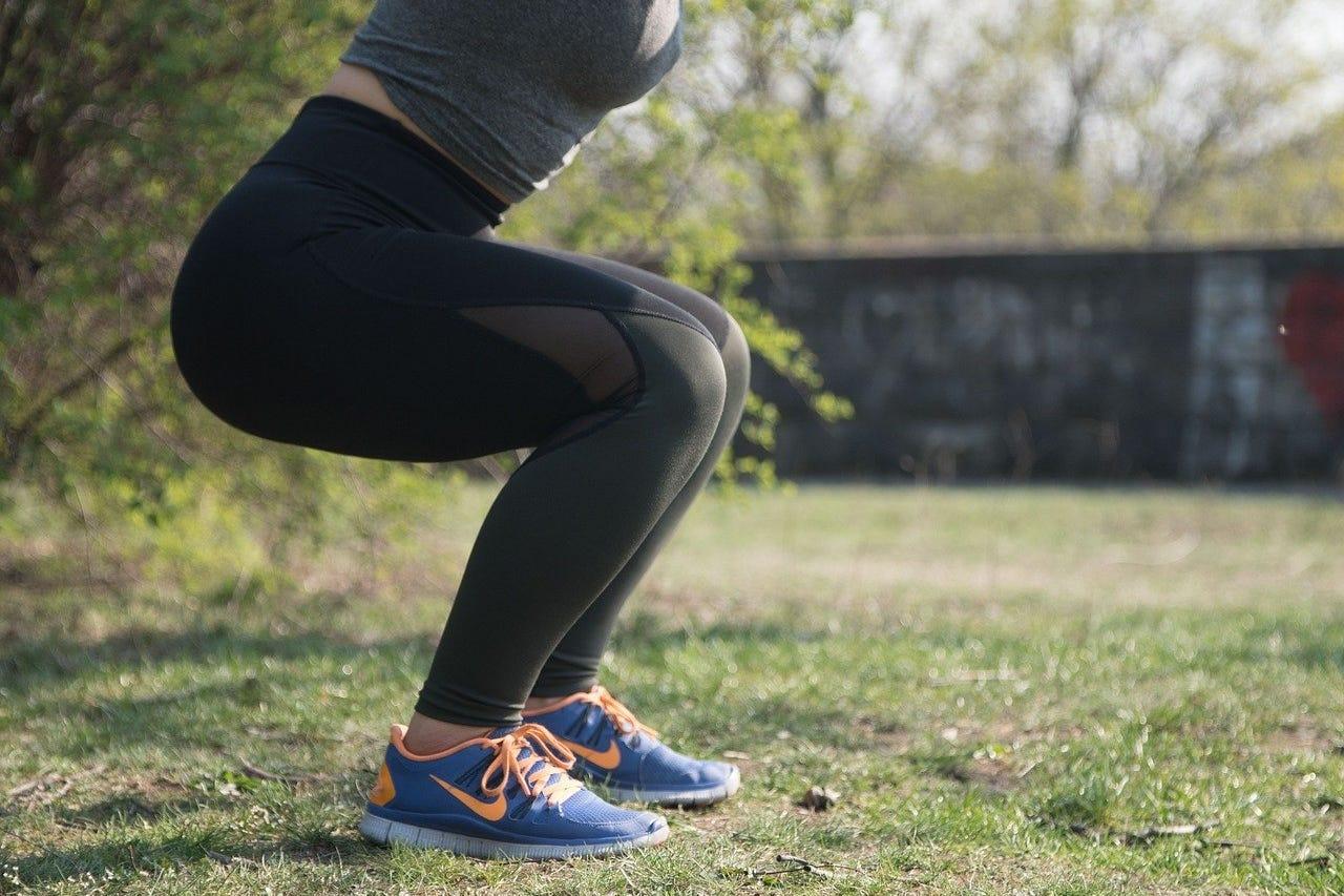 vrouw tuin squat training buiten legging