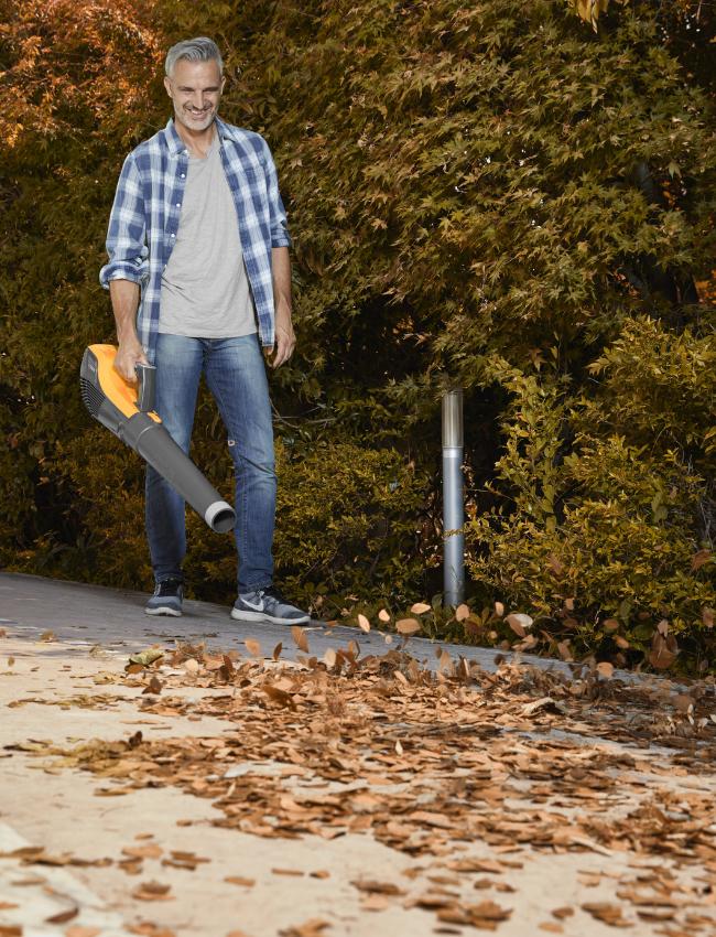 Man cleaning sidewalk with STIGA battery leaf blower