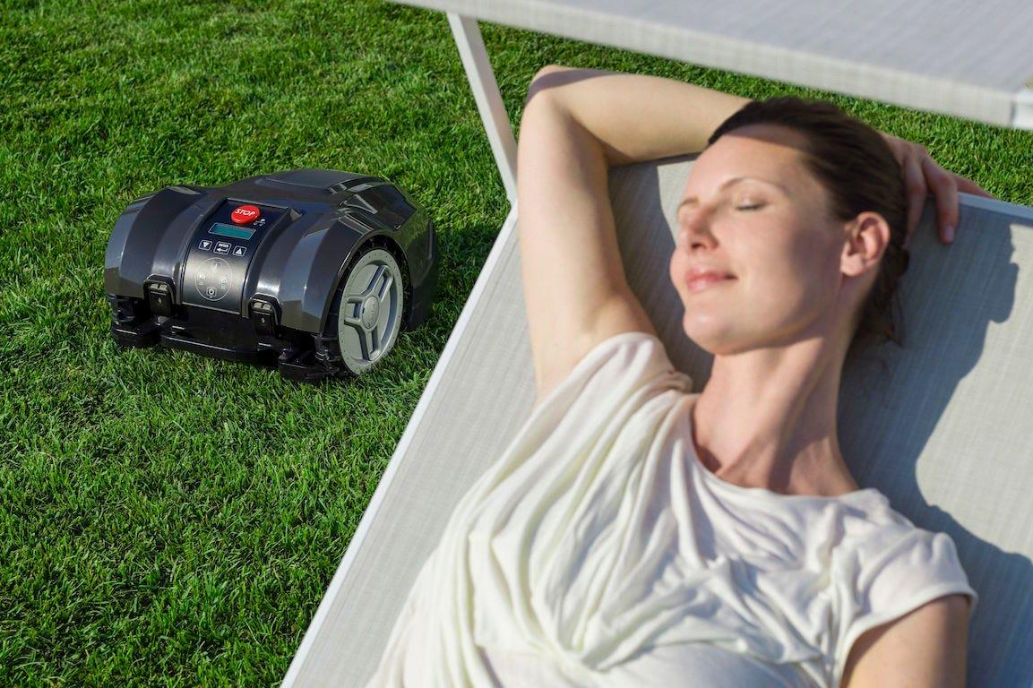 femme allongée dans un transat avec robot tondeuse STIGA Autoclip 225 S tondant le gazon