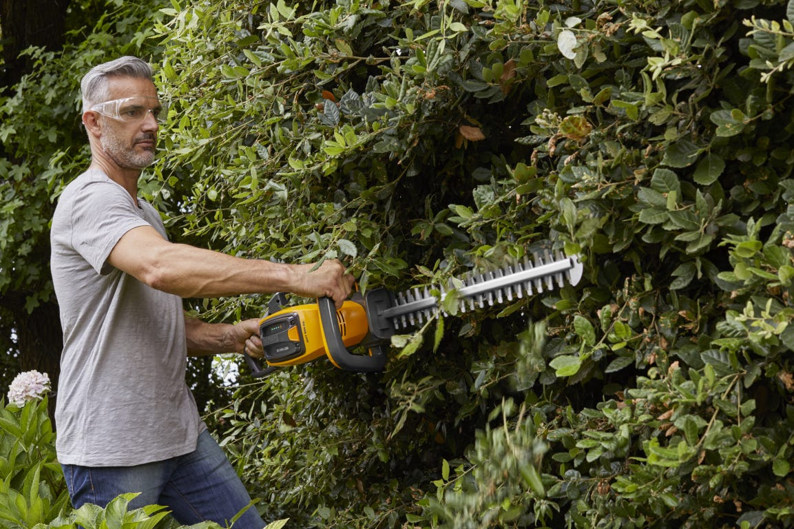 Man trimming hedge with STIGA battery powered SHT 500 AE hedgetrimmer