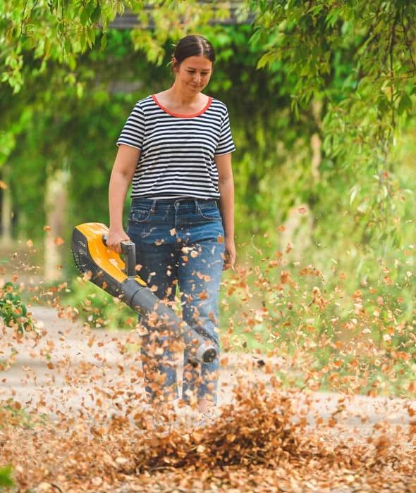 Nainen poistaa kuolleet syksyn lehdet akkukäyttöisellä lehtipuhaltimella