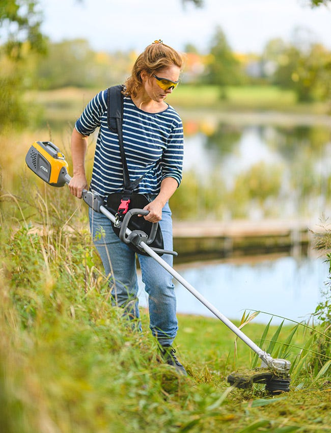 Woman cutting wild weeds with a STIGA battery brushcutter