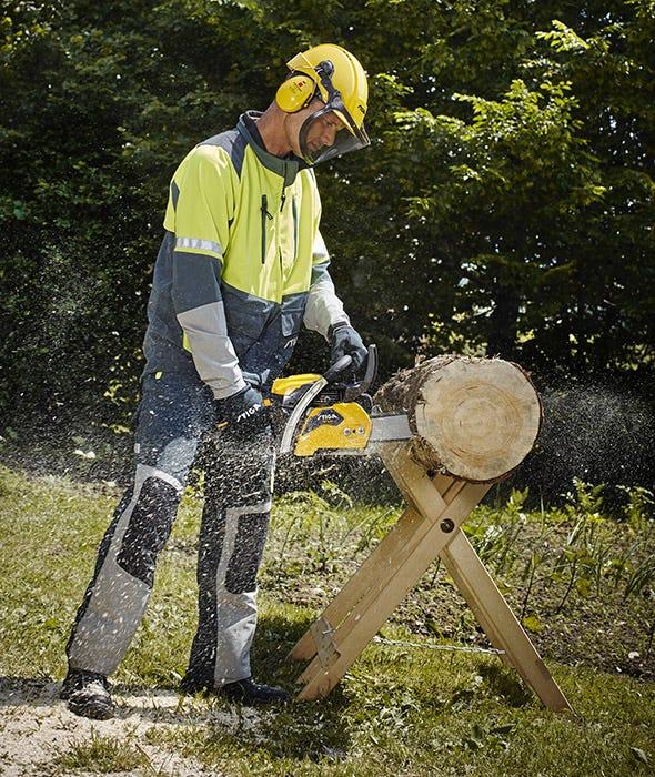Mies käyttää STIGA-mottorisahaa puun sahaamiseen