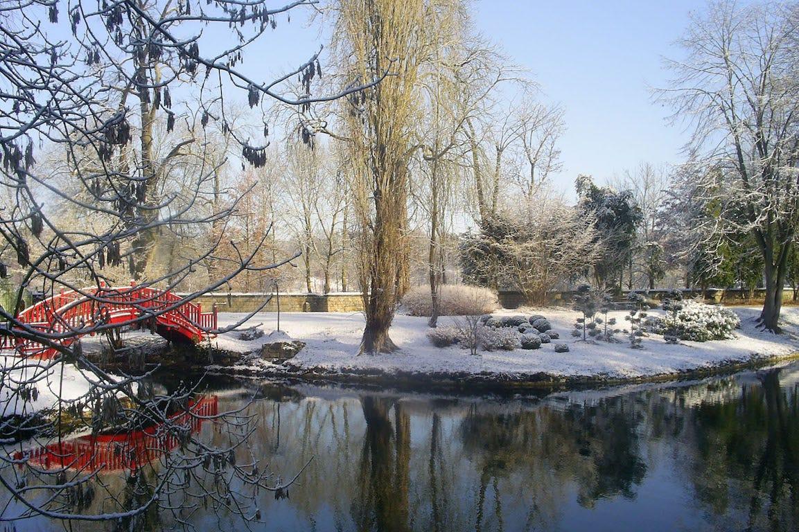 Jardin japonais au Potager des Princes à Chantilly dans l'Oise avec pont rouge et bassin sous la neige