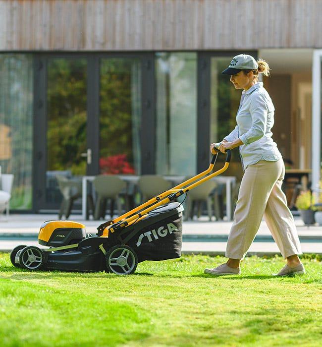 Femme tondant la pelouse derrière la maison avec une tondeuse à gazon STIGA Combi