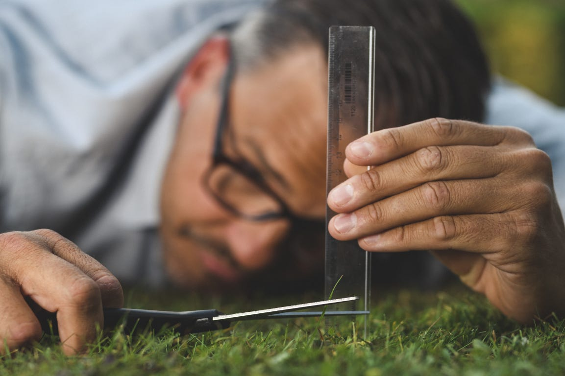 Man with glasses, ruler and scissors cutting the grass