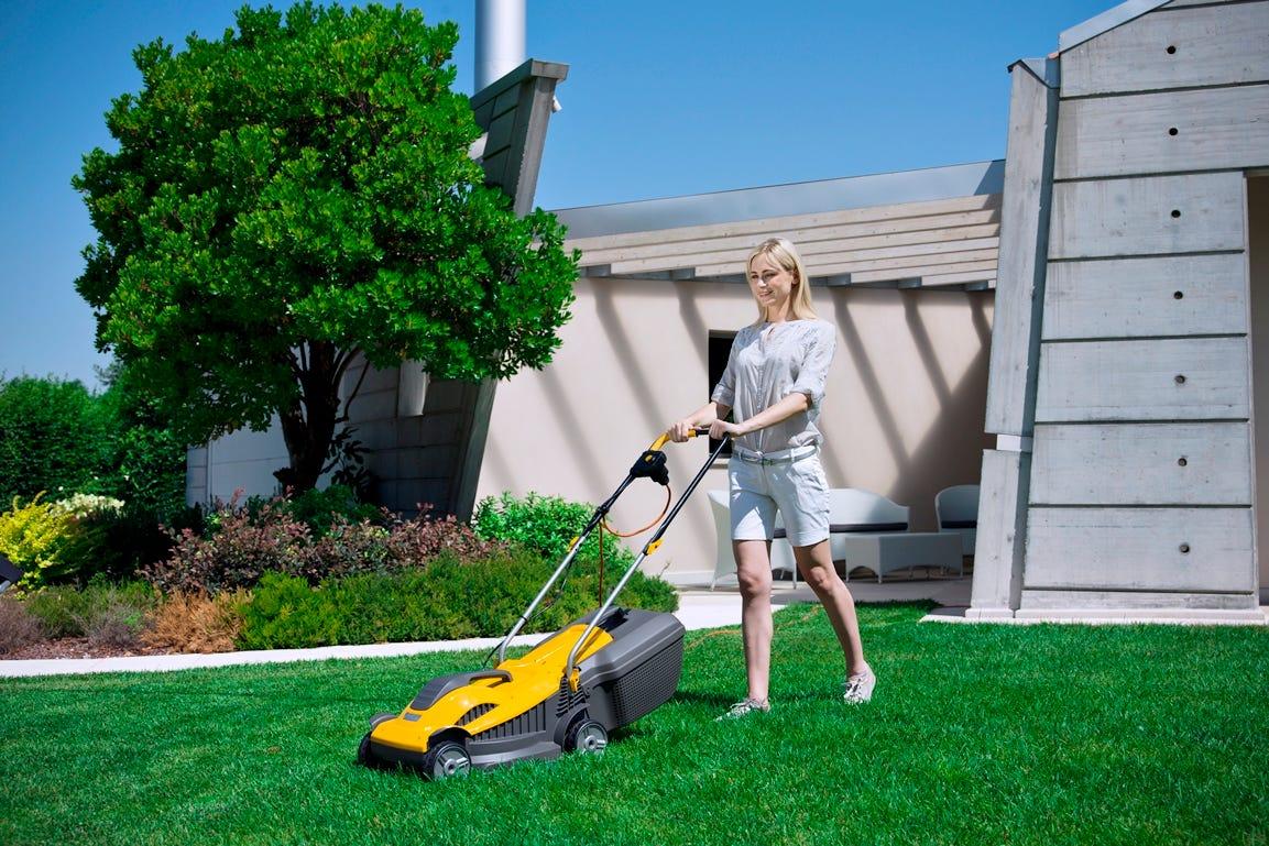 vrouw tuin groen gras maaien elektrisch grasmaaier geel