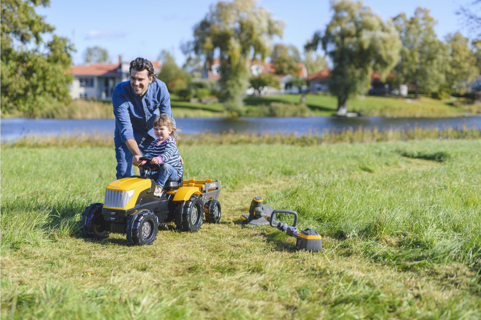 vader en dochter spelen in de tuin met gele stiga speelgoed tractor
