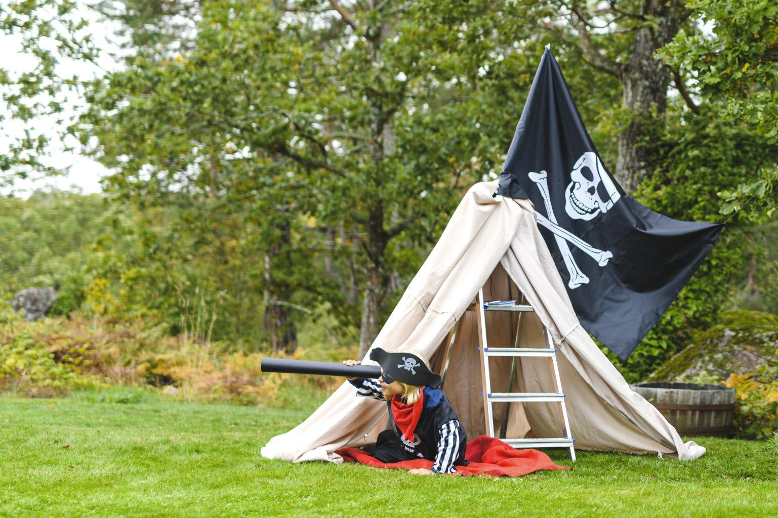 Jongen spelen in de tuin piraten met ladder en vlag met doodshoofd