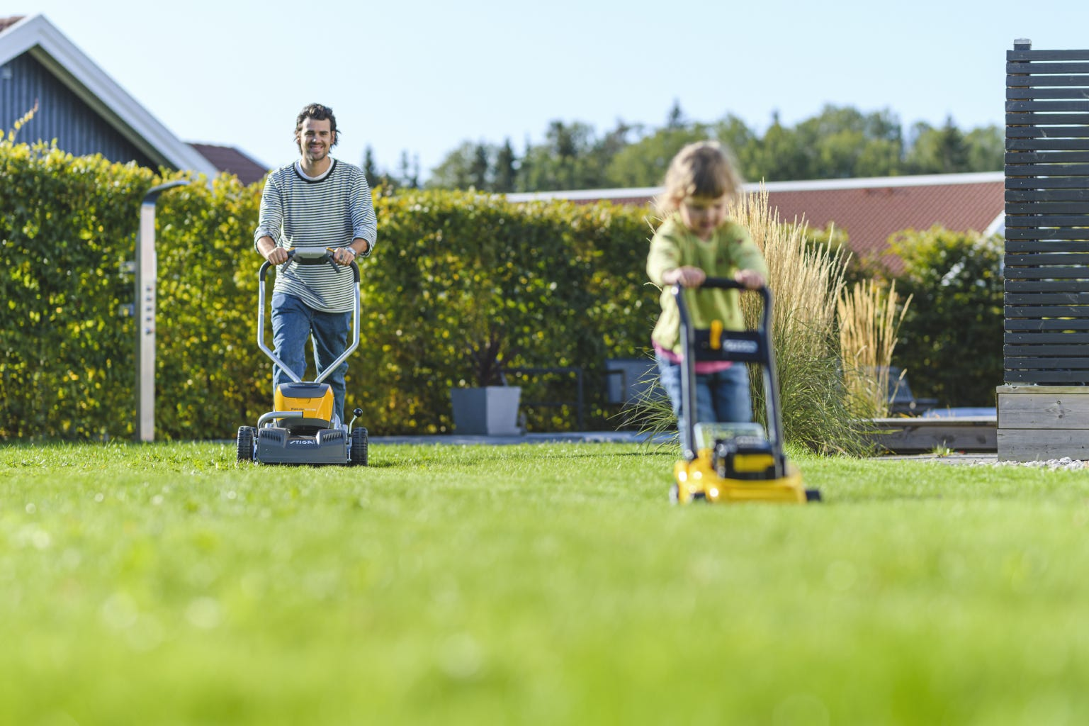 Dad and daughter mowing the lawn with battery lawn mower and yellow toy