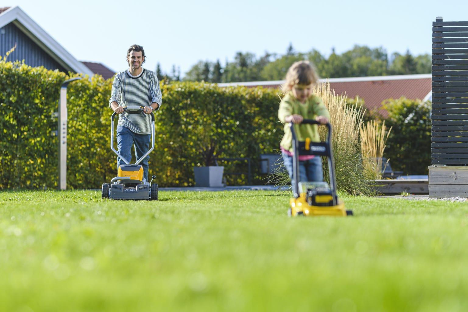 vader en dochter gras maaien met accumaaier en gele stiga speelgoed grasmaaier