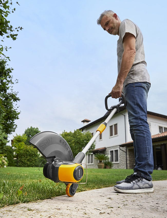 Man taking care of lawn edges with a STIGA battery lawn trimmer