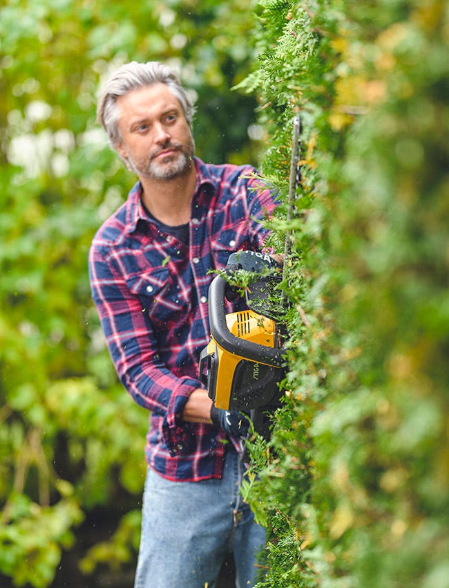 Man trimming hedge using a STIGA battery hedge trimmer