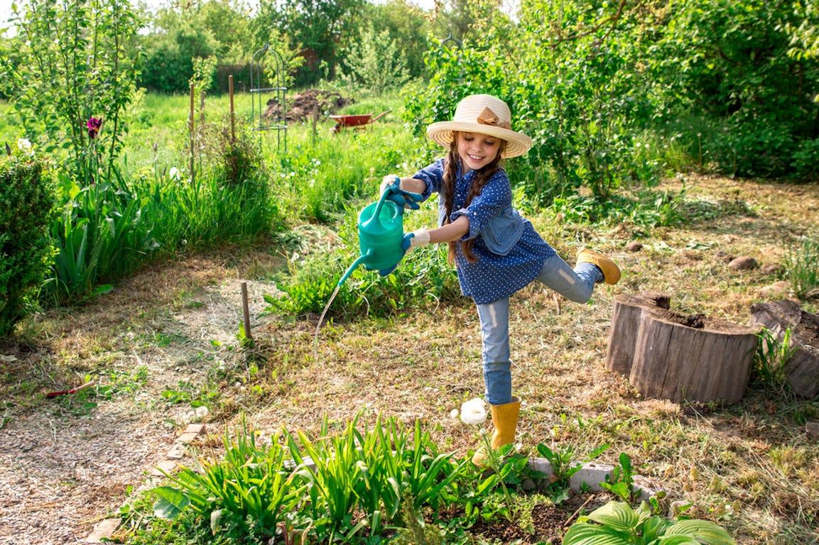 petite fille qui arrose des plantes dans un grand jardin