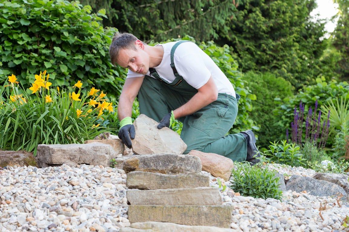 jardinier pose un pavé dans un jardin
