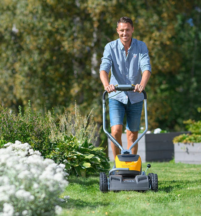 Nuori mies leikkaa nurmikkoa keltaisella Multiclip-ruohonleikkurilla