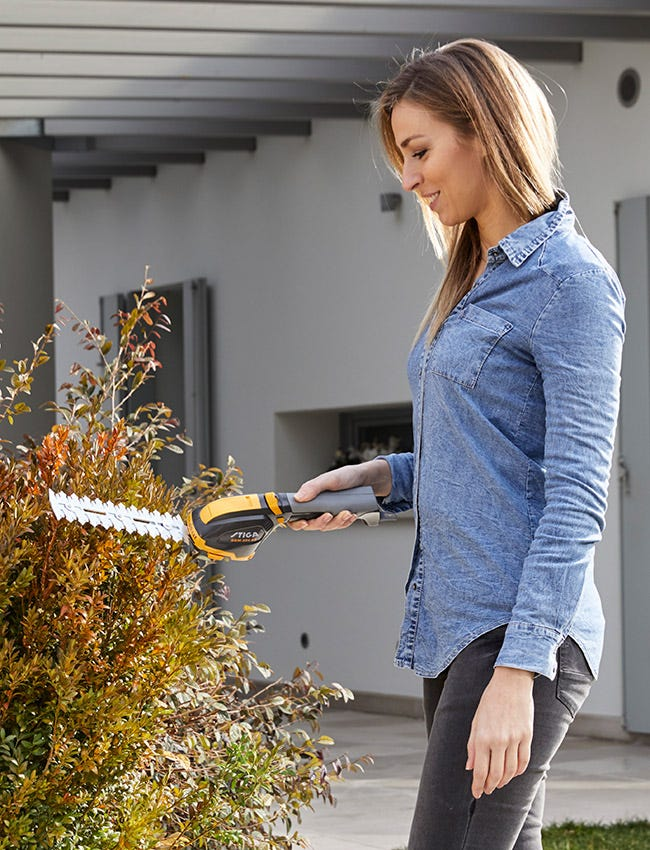 Young Woman standing with a STIGA battery hedge trimmer