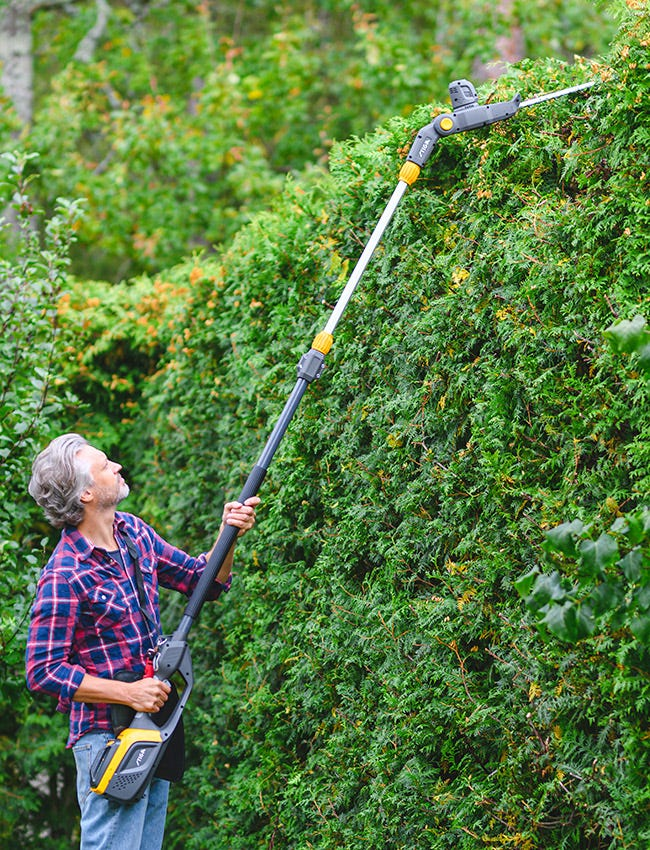 Man taking care of high hedge with a STIGA battery multi-tool