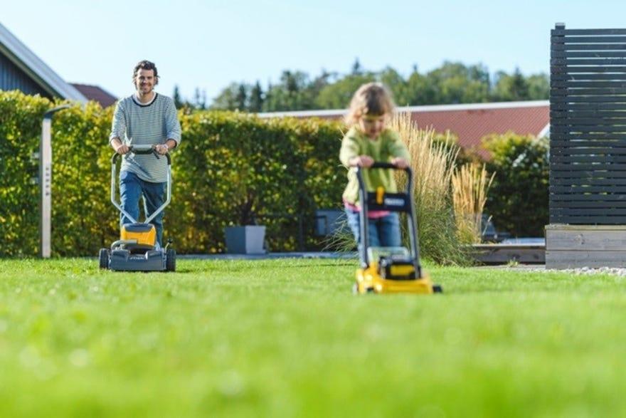 vader en kind met grasmaaier en speelgoed maaier in de tuin