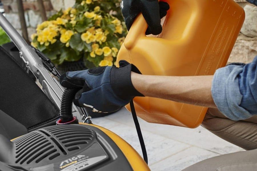 vrouw hand benzine in motor met bidon brandstof handschoen stiga