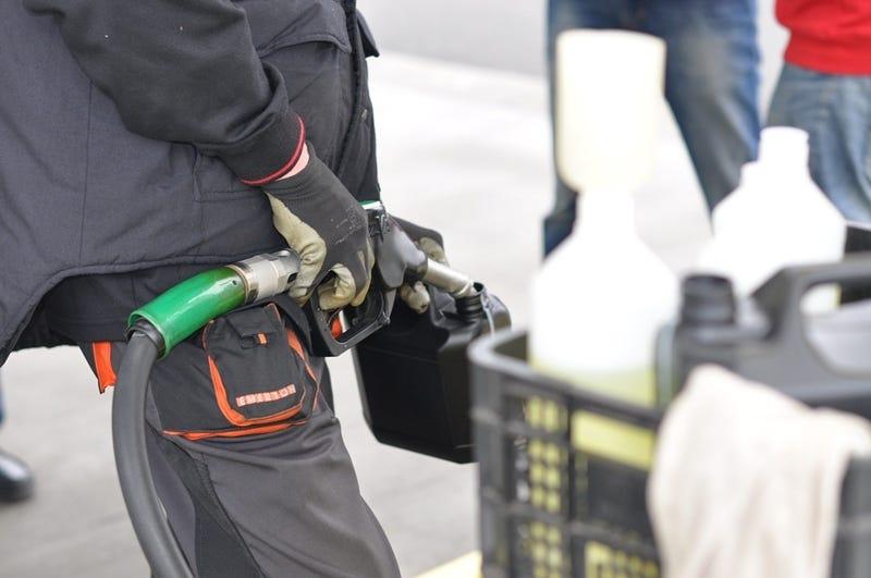 man brandstof tanken in tankstation met handschoen en bidon