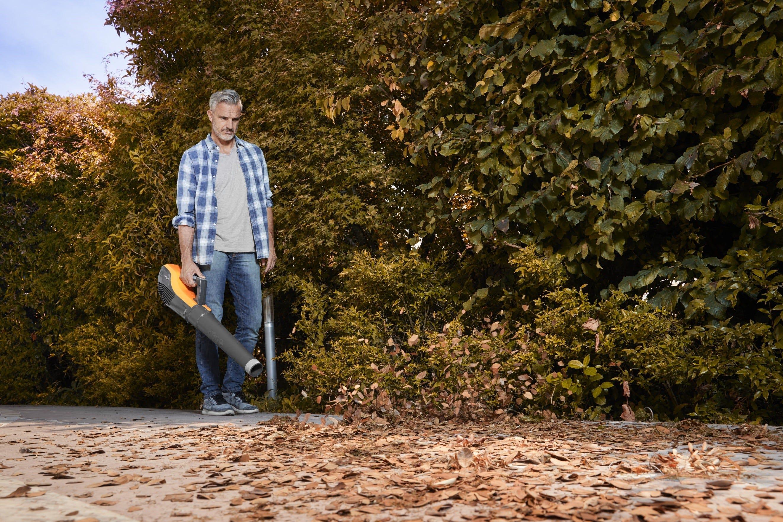 man met stiga bladblazer op accu bladeren ruimen