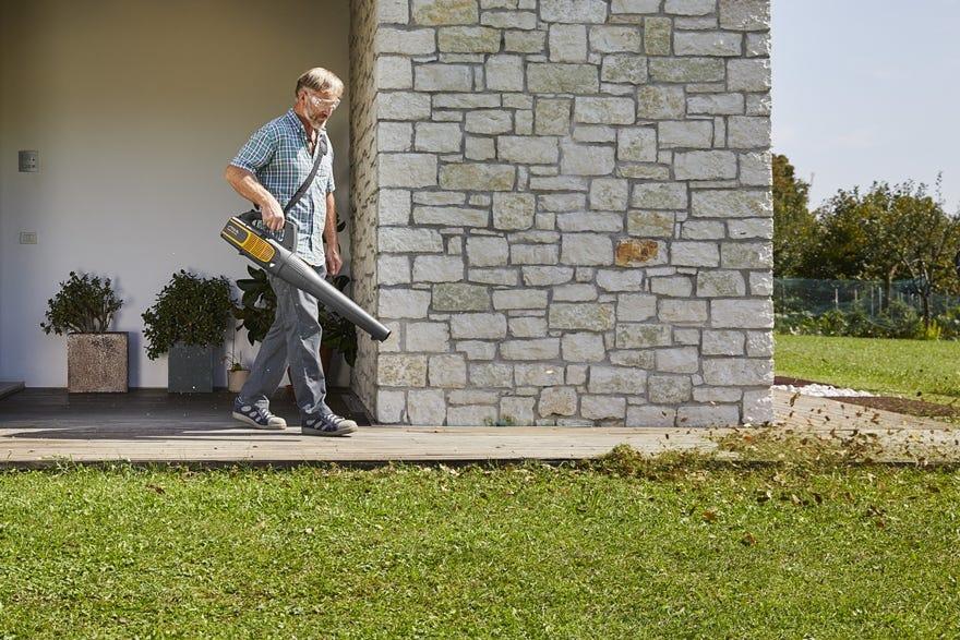 man met stiga bladblazer op accu bladeren in tuin