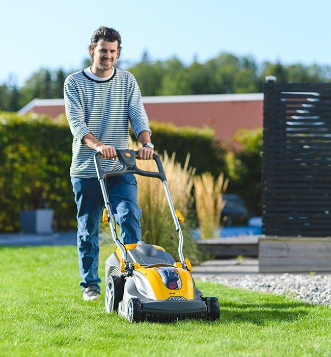 Nuori mies leikkaa nurmikkoa talon vieressä akkukäyttöisellä STIGA SLM -ruohonleikkurilla