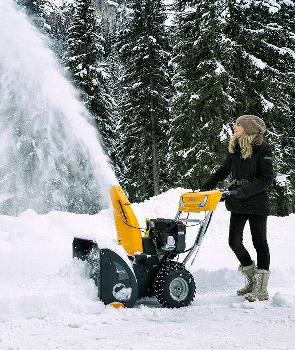 Woman clearing fresh white snow with STIGA petrol snow thrower