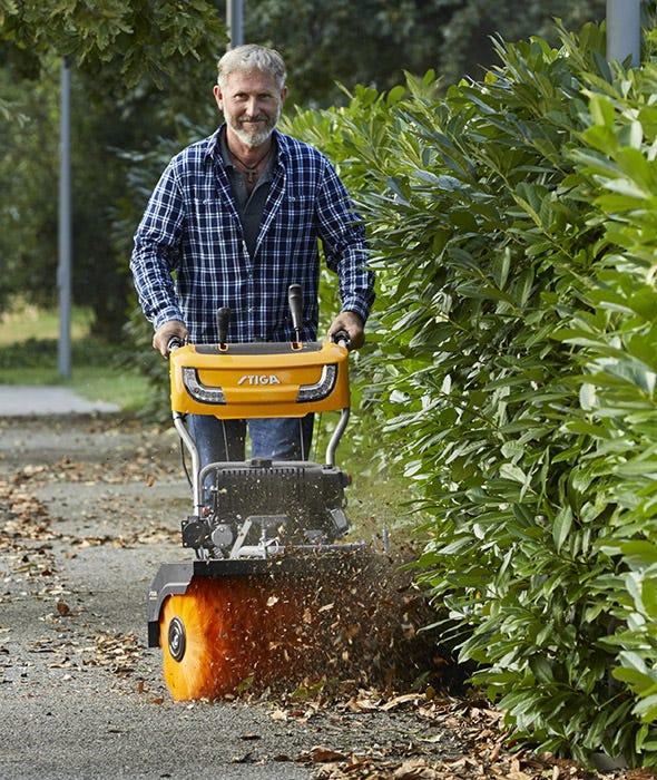 Mies puhdistaa kuolleet lehdet polulta lähellä vihreää pensasaitaa