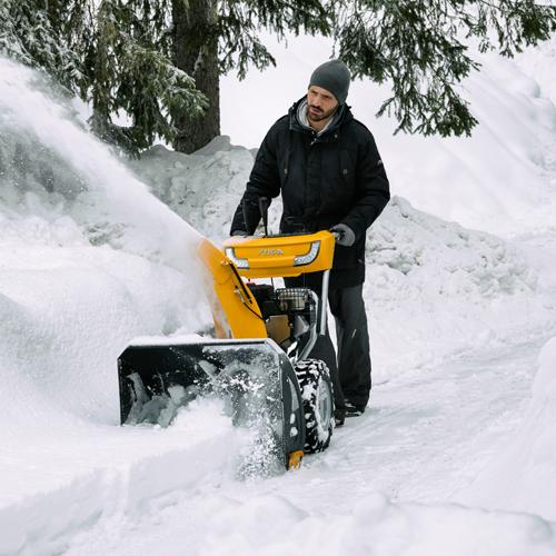 Mies työntää STIGA-lumilinkoa tuoreessa valkoisessa lumessa