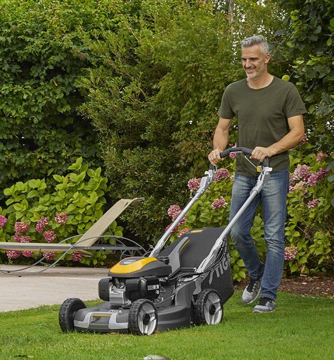Mies leikkaa nurmikkoa STIGA Twinclip -ruohonleikkurilla