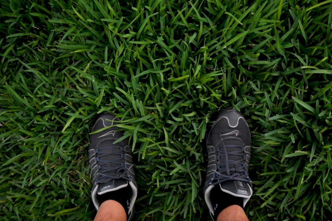 Voeten in het gras weelderig groen gazon